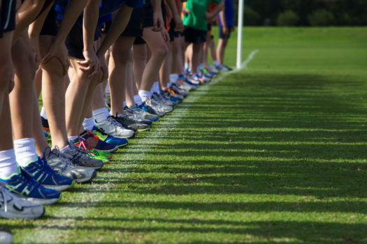Runners lined up on grass starting line