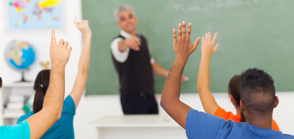 Students with hands up in classroom