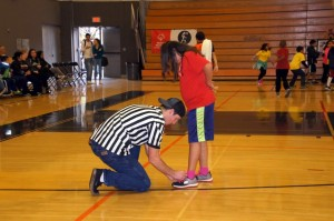 Basketball referee helping tie a special olympics player tie his shoe.