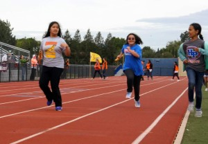 special olympics kid being cheered on while running